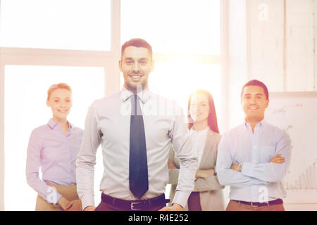 smiling businessman in office with team on back - Stock Photo