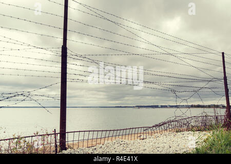 barb wire fence over gray sky and sea - Stock Photo