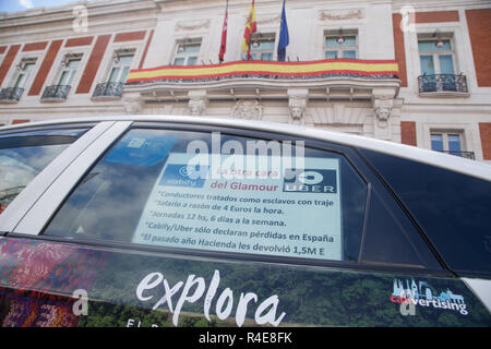 A placard seen on the glass of a taxi explaining some of the working conditions of Uber and Cabidy drivers during the protest. Some 5,000 taxi drivers called for the 'immediate and effective' regulation of the vehicle rental sector with driver (VTC) such as Uber or Cabify. The demonstration began at the government headquarters of the Community of Madrid at Puerta del Sol and ended at Plaza de Cibeles in front of Madrid City Hall. - Stock Photo