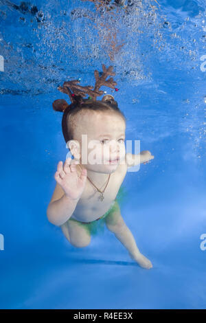 Odessa, Ukraine, Europe. 14th Nov, 2018. Little girl swim underwater in the swimming pool. It floats and spins among the air bubbles on a blue water background. Healthy family lifestyle and children water sports activity. Child development, disease prevention Credit: Andrey Nekrasov/ZUMA Wire/Alamy Live News - Stock Photo