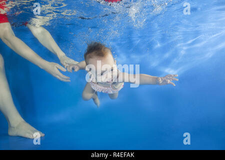 Odessa, Ukraine, Europe. 17th Nov, 2018. Little baby learns to swims underwater. Baby swimming underwater in the pool, mother holding the child. Healthy family lifestyle and children water sports activity. Child development, disease prevention Credit: Andrey Nekrasov/ZUMA Wire/Alamy Live News - Stock Photo
