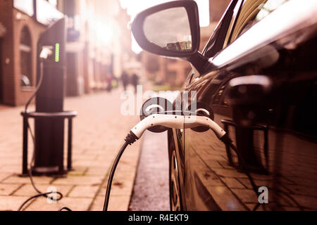 Electric car is changing on street parking in UK - Stock Photo
