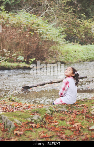 Girl sitting by a creek in autumn, Pacific Northwest, United States - Stock Photo
