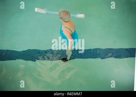 Senior Woman Exercising in Pool - Stock Photo