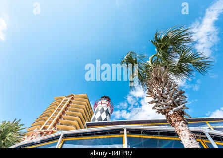Destin, USA - April 24, 2018: City town village Pirate's Alley cityscape looking up low angle on Harbor Boardwalk during sunny day in Florida panhandl