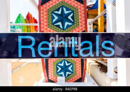 Destin, USA - April 24, 2018: Closeup of rentals sign with colorful kayak and surfboard boats in city town village on Harbor Boardwalk in Florida panh - Stock Photo