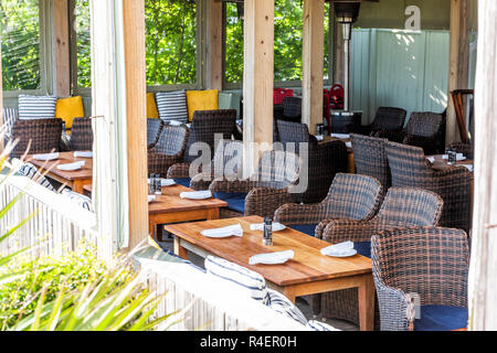 Seaside, USA - April 25, 2018: Waterfront seafood restaurant wooden tables in Florida with covered roof by beach ocean with empty, nobody seats, chair - Stock Photo