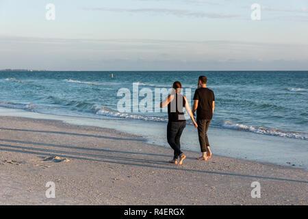Sarasota, USA - April 27, 2018: Sunset in Siesta Key, Florida with coastline coast ocean gulf mexico on beach shore, young couple romantic people walk - Stock Photo