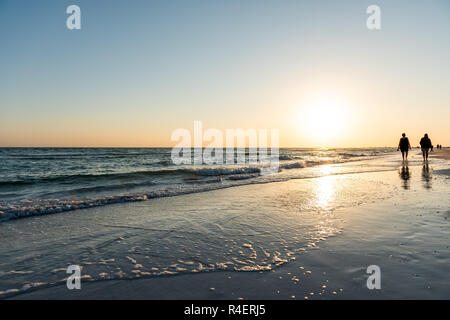 Sarasota, USA Sunset in Siesta Key, Florida with coastline coast ocean gulf of mexico on beach shore, people silhouette walking by waves - Stock Photo
