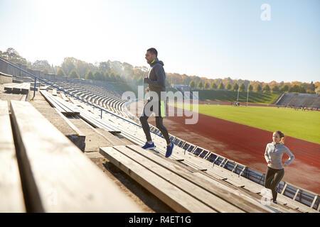 happy couple running upstairs on stadium - Stock Photo