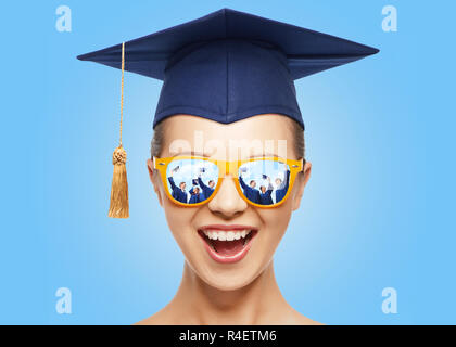 happy teenage girl in shades and mortarboard hat - Stock Photo