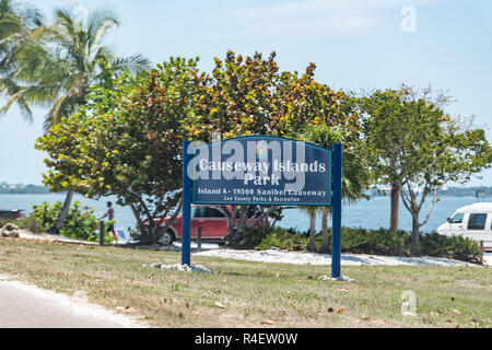 Sanibel Island, USA - April 29, 2018: Causeway Islands park sign by beach with cars, people on coast by Fort Myers, Florida - Stock Photo