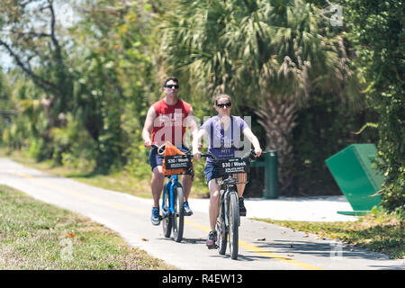 Sanibel Island, USA - April 29, 2018: Captiva people riding bikes bicycles on trail sidewalk in park by beach and road in Fort Myers, Florida - Stock Photo