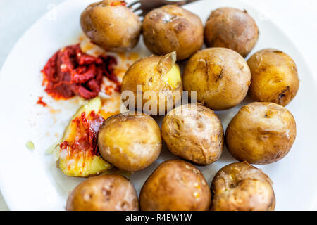 Closeup flat table top view of fresh boiled steamed baked small potatoes on white plate with tomato paste ketchup, fork, many tubers - Stock Photo