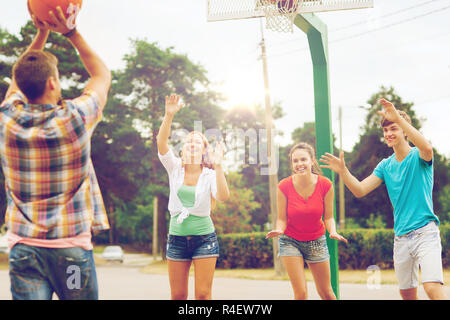 group of smiling teenagers playing basketball - Stock Photo