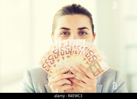 woman hiding her face behind euro money fan - Stock Photo