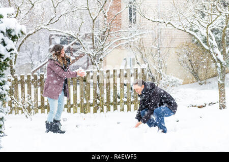 Young man, woman playing, making, sitting, standing, throwing snowballs in winter snowstorm, storm, snowing at home, house garden, front yard, backyar - Stock Photo