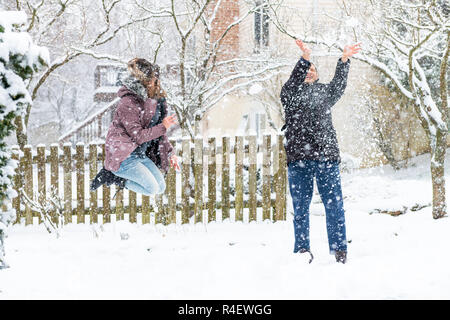Young woman jumping mid-air, air, playing, throwing snowballs at man in winter snowstorm, storm, snowing at home, house garden, front yard, backyard,  - Stock Photo