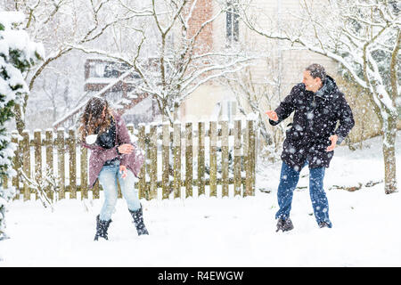 Young man, woman playing, throwing flying snowballs mid-air, air in winter snowstorm, snowing at home, house garden, front yard, backyard, trees cover - Stock Photo