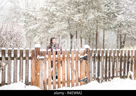 One young woman standing in front of wooden home, house fence outside, outdoors, outdoor front yard, backyard in heavy snowstorm, storm, snowing, fall - Stock Photo
