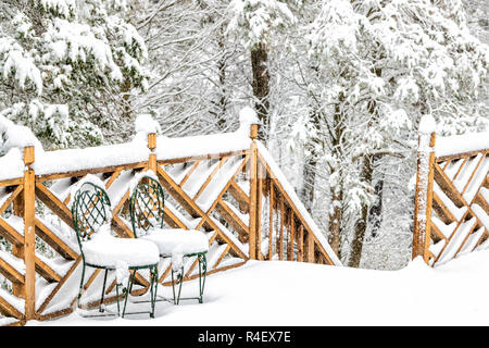 Snow covered house, home wooden deck with two cast iron chairs, snowing, falling snowflakes, snowstorm, storm, trees, forest in backyard, front yard,  - Stock Photo