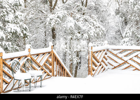 Forest, snow covered house, home wooden deck with two cast iron chairs, snowing, falling snowflakes, snowstorm, storm, trees in backyard, front yard,  - Stock Photo