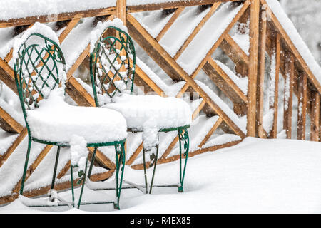 Closeup of two cast iron chairs covered in snow on home, house wooden deck, railing, fence in winter, snowing, falling snowflakes, snowstorm, storm in - Stock Photo