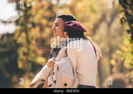 Beautiful, young couple is spending nice day in the autumn park, looking peacfully while hugging - Stock Photo