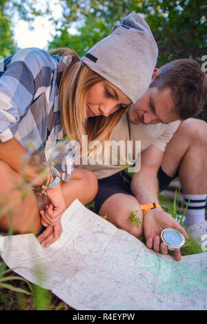 Young couple navigasting using map and compass inside the forest. Hiking concept in the mountain in summer - Stock Photo