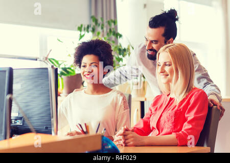 happy creative team with computer in office - Stock Photo