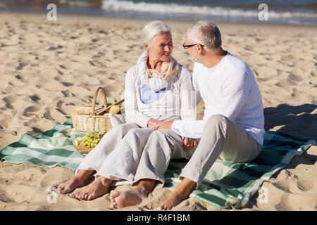 happy senior couple having picnic on summer beach - Stock Photo