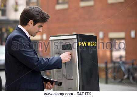 A businessman putting coins in a parking meter - Stock Photo
