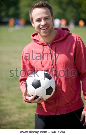 A young man standing in the park, holding a football - Stock Photo