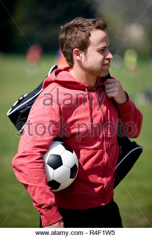 A young man standing in the park, carrying a football and a sports bag - Stock Photo