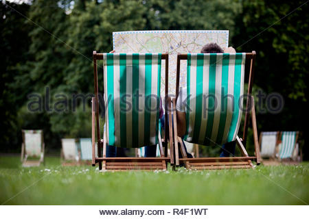 A young couple sitting on deckchairs in St James Park, looking at a map - Stock Photo
