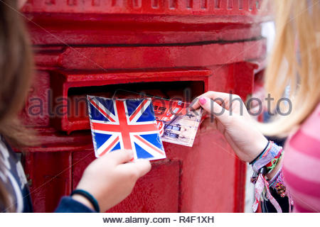 Two teenage girls putting postcards into a red letterbox - Stock Photo