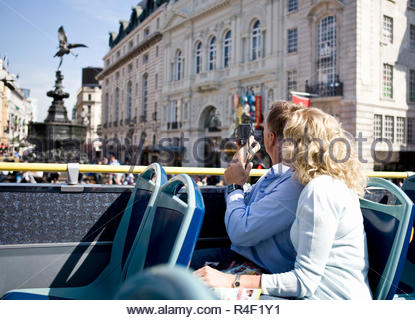 A middle-aged couple sitting on a sightseeing bus, taking photographs - Stock Photo