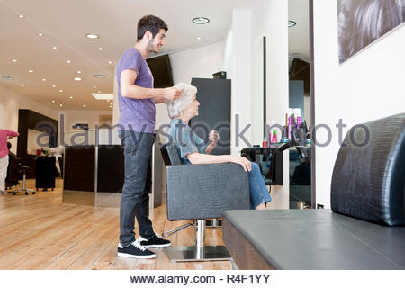 A male hairdresser discussing a female clients hair - Stock Photo