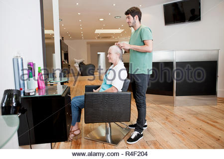 A male hairdresser applying product to his female clients hair - Stock Photo