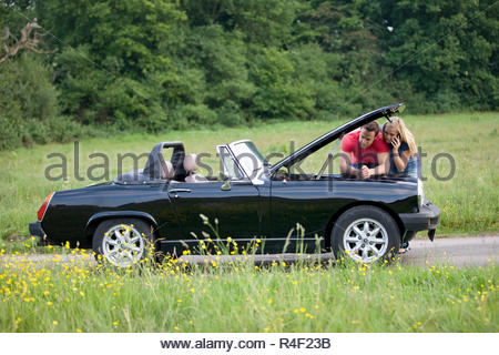 A young couple standing next to their broken down sports car speaking on a mobile phone - Stock Photo