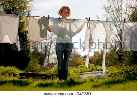 A mature woman pegging out washing on a washing line, rear view - Stock Photo