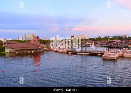 Orlando, Florida. November 19, 2018 Panoramic view of Volcano reflecting in lake, vintage bridge and outside market on sunset with magenta rays at Lak - Stock Photo
