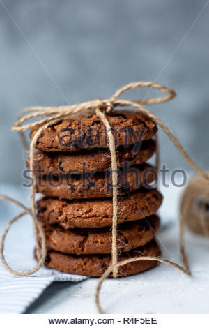 Festive chocolate cookies tied with red isolated on light background. - Stock Photo