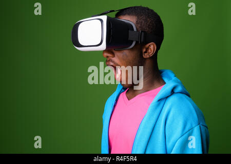 Studio shot of young African man against green background - Stock Photo