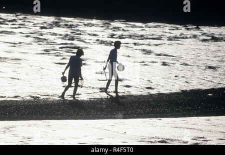 Two girls playing in the mud at low tide, Boothbay, Maine, USA - Stock Photo