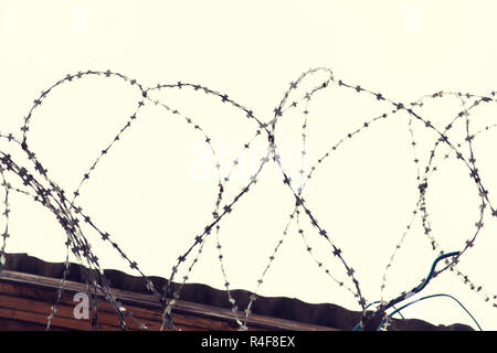 barb wire fence over gray sky - Stock Photo