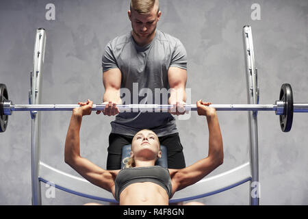 man and woman with barbell flexing muscles in gym - Stock Photo