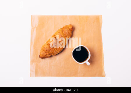 Flat lay composition of simple breakfast of croissant and cup of black coffee on brown baking paper, top view on white background. - Stock Photo