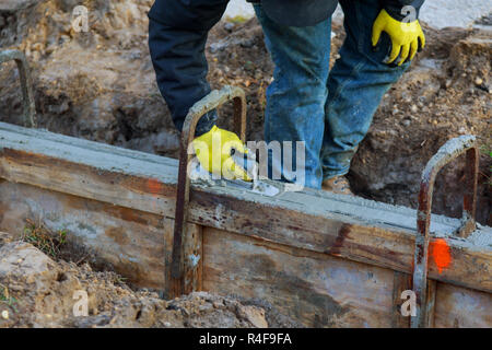 Construction workers leveling concrete pavement. Masonry construction workers - Stock Photo