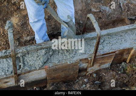 Masonry construction workers pouring cement during to residential street upgrade - Stock Photo